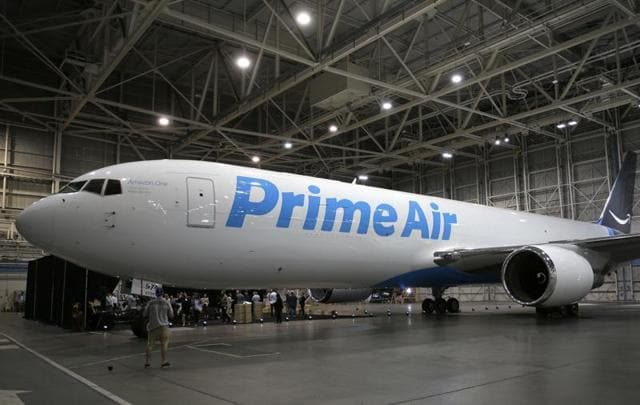 Amazon.com boxes are stacked near a Boeing 767 Amazon