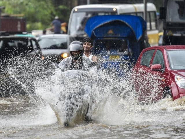 People wade through a flooded street during heavy rains in Mumbai.