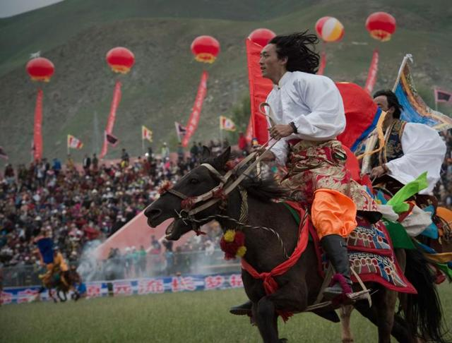 Tibetans ride horses in traditional dress, showing their skills at a local government sponsored festival in Yushu, in the northwestern Chinese province of Qinghai.