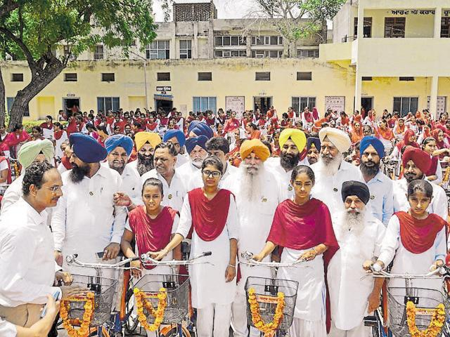 Balbir Singh Ghunas (centre) at the function where he distributed bicycles to government school girls in Mansa, on Thursday.