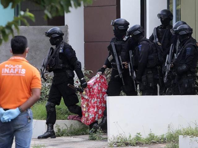 Indonesian anti-terror police seen entering a building during a raid in Batam, Riau Islands, on Friday in this photo taken by Antara Foto.