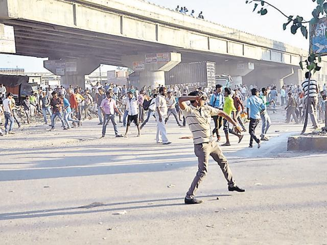 Agitators pelting stone at policemen in Chakeri area of Kanpur following the death of a Dalit youth in police custody under  suspicious circumstances.