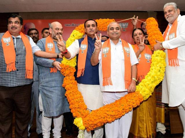 Newly elected Gujarat CMVijay Rupani (in a blue jacket) and deputy CM Nitin Patel (third from right) garlanded by BJP president Amit Shah (second from left), Union minister Nitin Gadkari (extreme left) and Purushottam Rupala after a meeting at Gujarat BJP headquarters 'Kamlam' at Gandhinagar on Friday.
