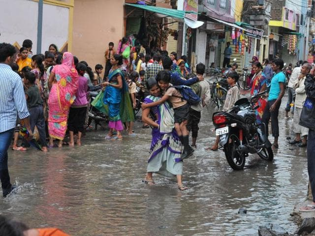 School children in Krishnabagh Colony walk on submerged roads in front of a school in Indore on Thursday.