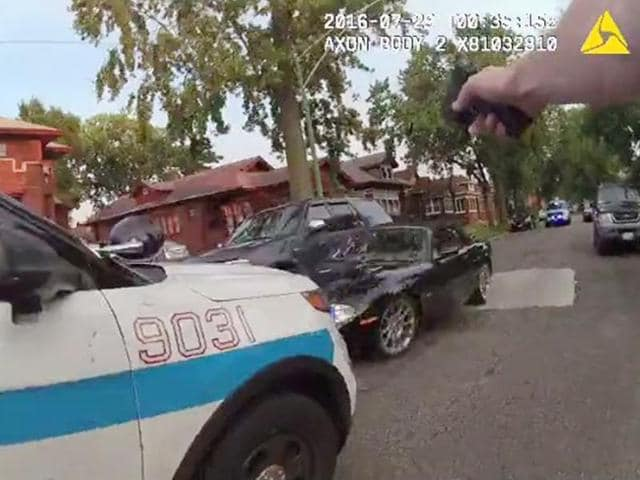 A Chicago police officer is seen shooting his weapon at a moving car (centre) in this still image from a video taken from a body camera released by the Chicago police in Chicago, Illinois.