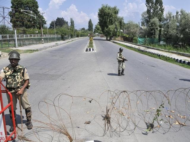 Paramilitary soldiers stand guard during curfew in Srinagar.