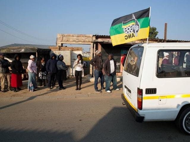 A taxi carrying the flag of the ruling African National Congress (ANC) party drives past locals queueing to cast their votes during the Local Government elections in Diepsloot township, north of Johannesburg, South Africa.