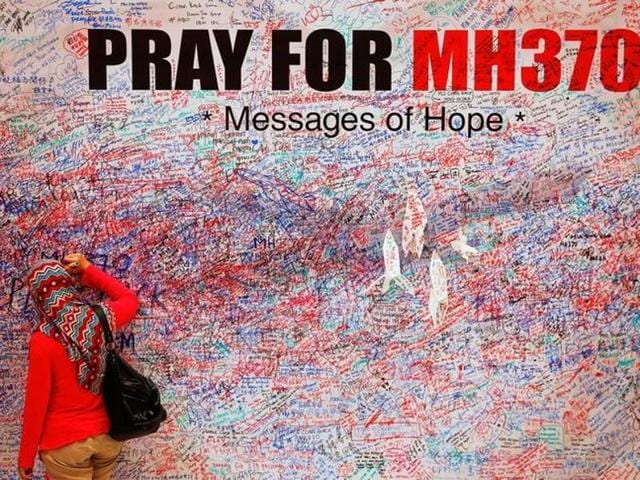 File photo of a woman leaves a message of support and hope for the passengers of the missing Malaysia Airlines MH370 in central Kuala Lumpur March 16, 2014.