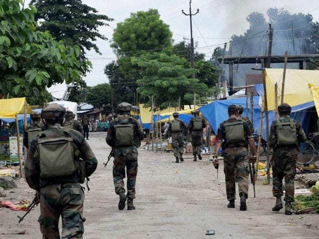 Security personnel patrol a market area after an attack by NDFB (S) terrorists in Kokrajhar town in Assam.