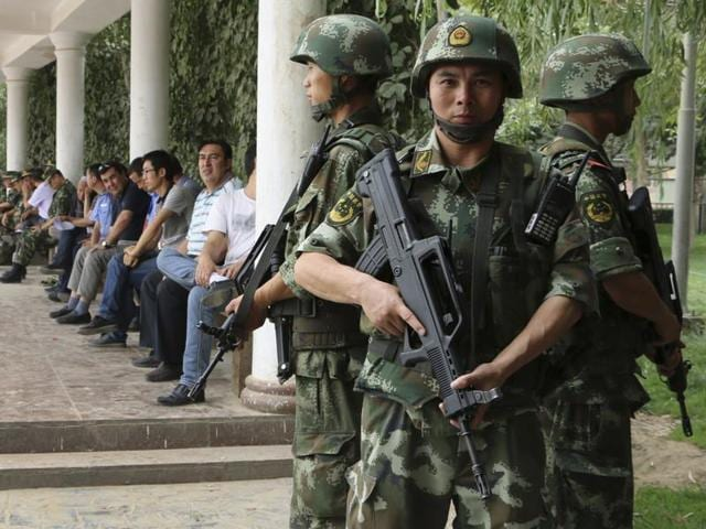 Paramilitary policemen patrol past a building in the Xinjiang Uighur Autonomous Region.(Reuters File)