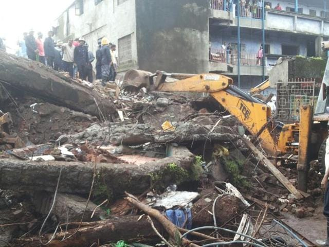 Rescuers remove the rubble of the two-storey building that collapsed early on Sunday killing two people and injuring six others.