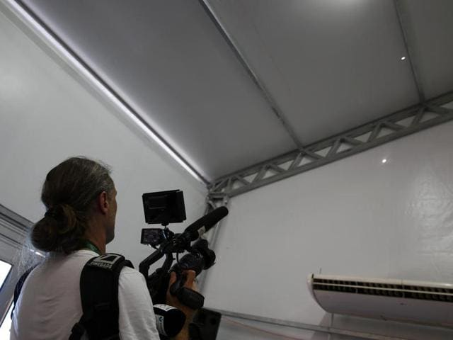 A TV cameraman films two holes in the tent that serves as a media centre for the Deodoro Olympic Equestrian Center  in Rio on Saturday. Security officials are investigating reports that a bullet tore through the tent.