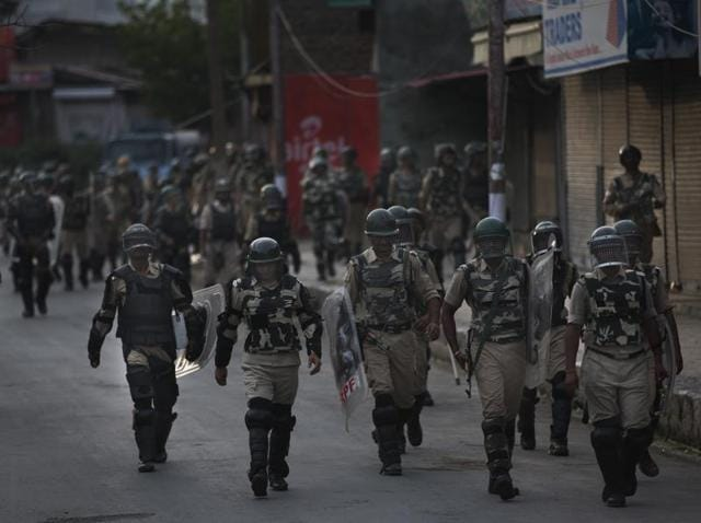 Soldiers walk back towards their base camp after a day long curfew in Srinagar.