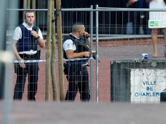 Belgian police officers stand guard outside the main police station after a machete-wielding man injured two female police officers before being shot in Charleroi, Belgium.