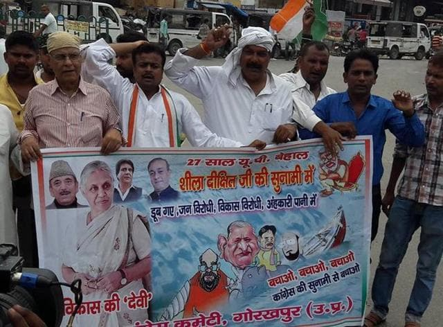 Congress workers with the poster showing Sheila Dikshit as 'goddess of development', in Gorakhpur on Sunday.