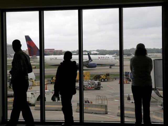 A passenger talks on her phone at a Delta Airlines gat at the Salt Lake City international airport.