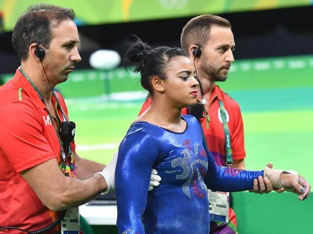 Britain's Elissa Downie speaks with her coach after an injury dueing qualifying for the women's floor event of the Artistic Gymnastics.