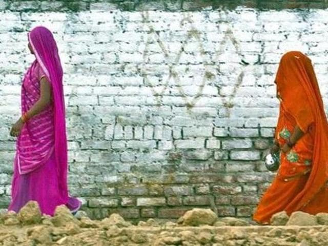 Women return after defecating in an open field in a village in the Badaun district of Uttar Pradesh.(AFP File Photo)