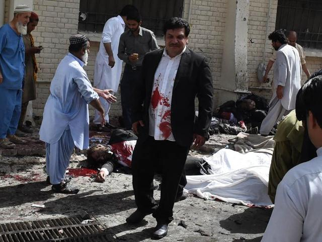 Pakistani volunteers use a trolley to move the body of a lawyer after a suicide attack at the Civil Hospital in Quetta on Monday. At least 70 people were killed in the attack in the southwestern Pakistani city.
