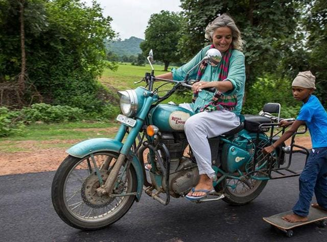 Ulrike Reinhard slowly drives her motorbike with a child on tow.