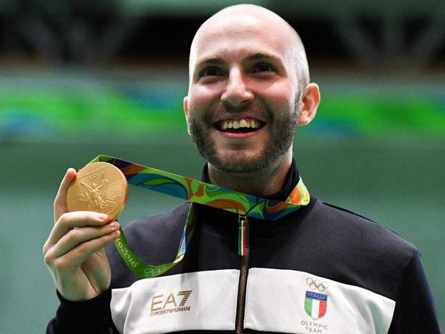 Gold medal winner Italy's Niccolo Campriani celebrates on the podium during the medal ceremony.