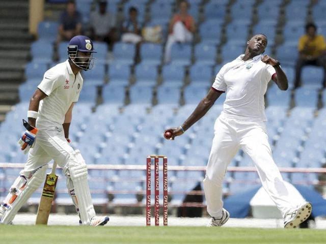 West Indies' captain Jason Holder bowls under the watch of India's batsman Lokesh Rahul.