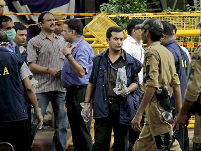 An officer of the NIA stands with the evidence collected from the site of a blast at Delhi high court in New Delhi.