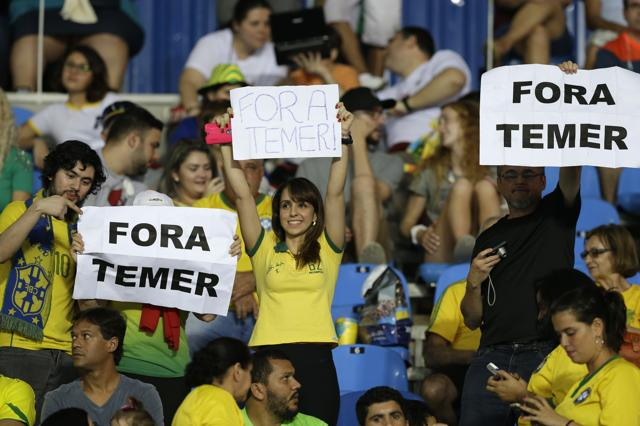 Fans at Rio's Olympic Stadium hold up signs that read in Portuguese;