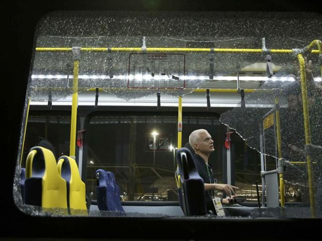 A person sits on an official media bus after a window shattered when driving accredited journalists to the Main Transport Mall from the Deodoro venue of the Rio 2016 Olympic Games in Rio de Janeiro, August 9, 2016.