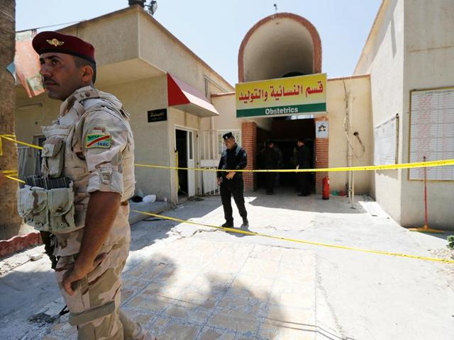 Iraqi security forces stand guard in front of a maternity ward after a fire broke out at Yarmouk hospital in Baghdad, Iraq.