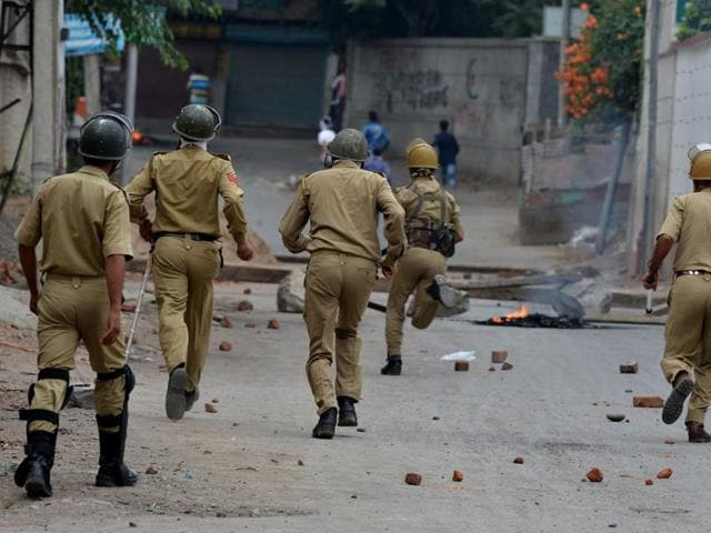 Government forces chase Kashmiri protesters during a clash in downtown Srinagar.