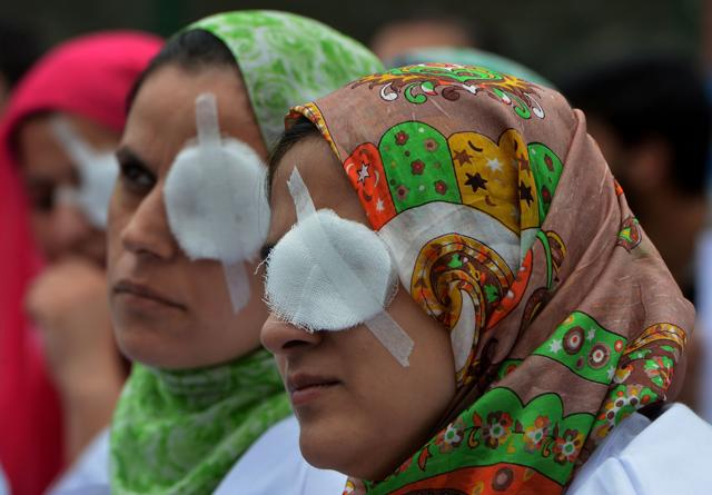 Kashmiri doctors and paramedics, their eyes covered by patches, take part in a protest at a hospital in Srinagar on August 10, 2016. The protesters covered one of their eyes to emulate the plight of the victims of pellet guns, who have been left partially or completely blind after being shot during ongoing protests.