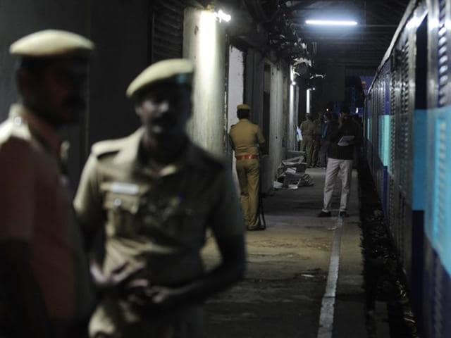 Police personnel stand guard alongside the Salem-Chennai Express train, which was robbed while in transit, at Egmore railway station in Chennai.