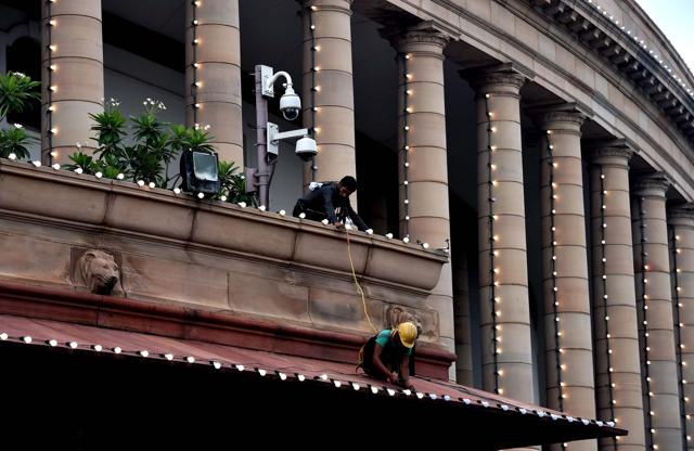 Workers install LED bulbs at Parliament House ahead of the Independence Day celebrations.