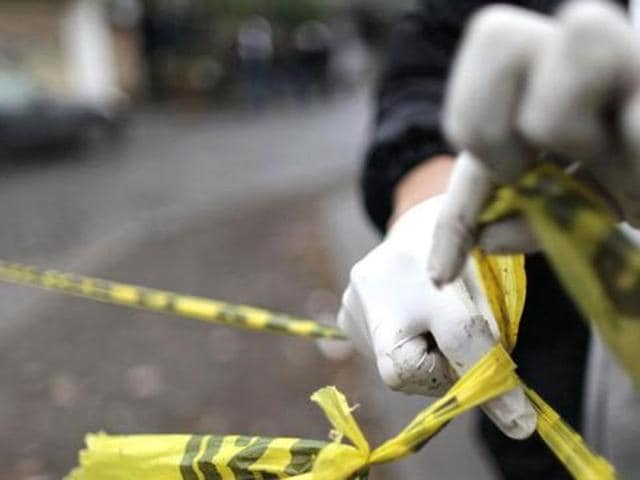 A forensic technician ties a police line together to seal off a crime scene.