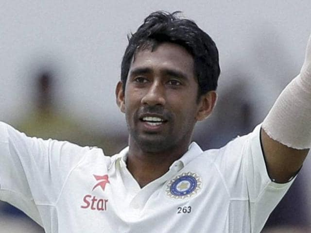 India's wicketkeeper Wriddhiman Saha celebrates after he scored a century against West Indies.