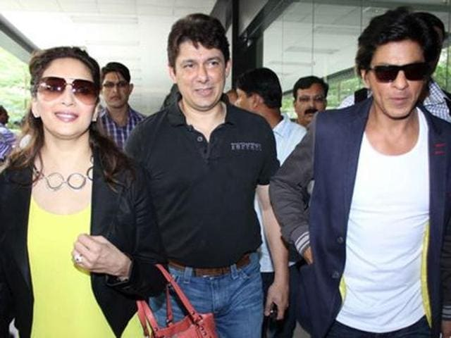 Shah Rukh Khan spotted at Mumbai Airport with Madhuri Dixit Nene, along with her hubby Sriram Nene, after completing their Temptation Reloaded concert in October 2013. (Pinterest)