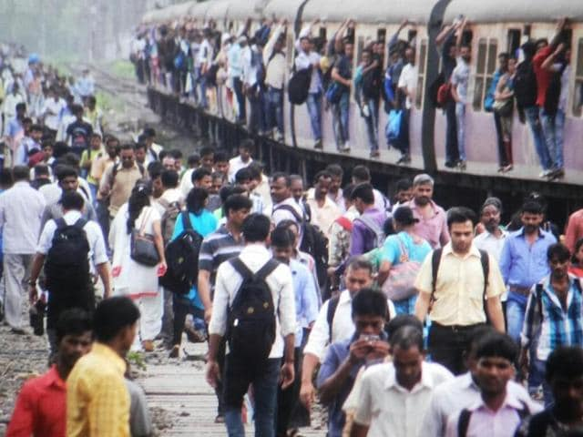 Passengers jostle to get into the train at Thane station on Friday morning.