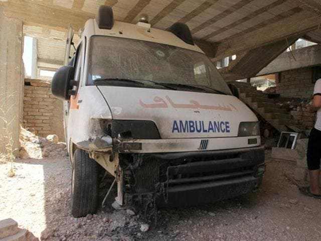 A man walks past a damaged ambulance after an airstrike hit Anadan Hospital of Anadan in northern Aleppo of Syria on July 31. At least 10 were killed in another airstrike Kafr Hamra town of Aleppo on Friday.