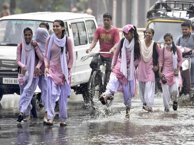 Students walking on the flooded Mall Road in Amritsar on Thursday.