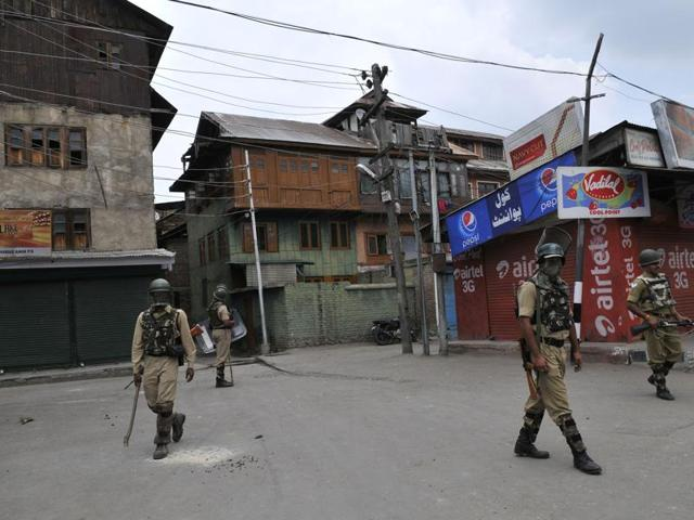 Paramilitary soldiers stand guard during curfew in downtown area of Srinagar.
