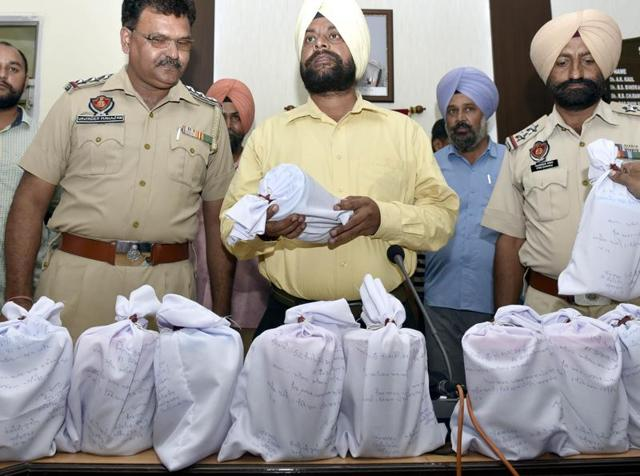 Cops showing the contraband in Amritsar on Thursday.