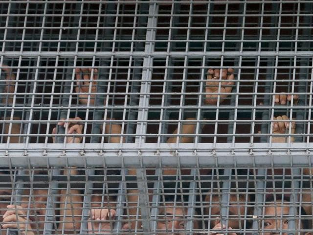 Prisoners hold on to the window grill as they communicate with their relatives below, hours after numbers of inmates, including alleged Chinese drug criminals, died in a suspected grenade blast at the Paranaque City Jail in suburban Paranaque city, south of Manila, Philippines on Friday.