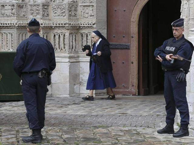 Armed French police stand guard as a nun leaves the Cathedral in Rouen after a funeral service in memory of slain French parish priest Father Jacques Hamel in Rouen, France, August 2, 2016.