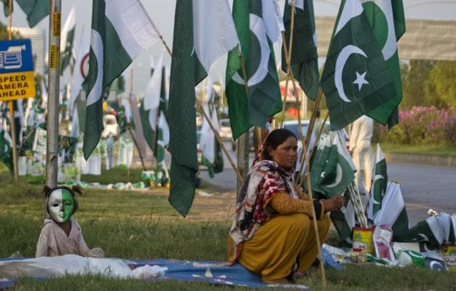 A vendor waits for customers with her daughter to sell national flags, badges and masks ahead of Pakistan's Independence Day in Islamabad.