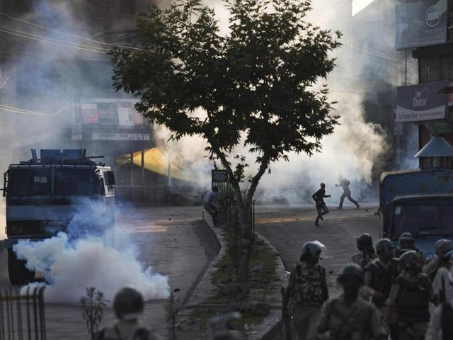 Kashmiri protesters run for cover from plumes of tear gas as soldiers walk back towards their base camp after a day-long curfew in Srinagar.