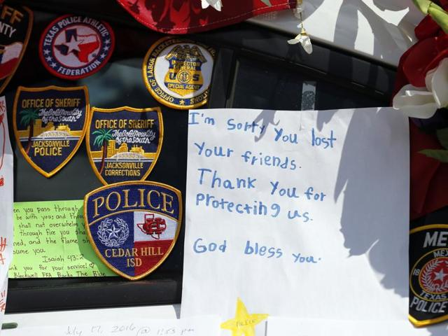 A note left behind attached to a police cruiser at a makeshift memorial in front of the headquarters of the Dallas Police Department sits surrounded by law enforcement badges, Tuesday, July 19, 2016, in Dallas. Five  police officers were killed by a gunman during a protest last month in Dallas.