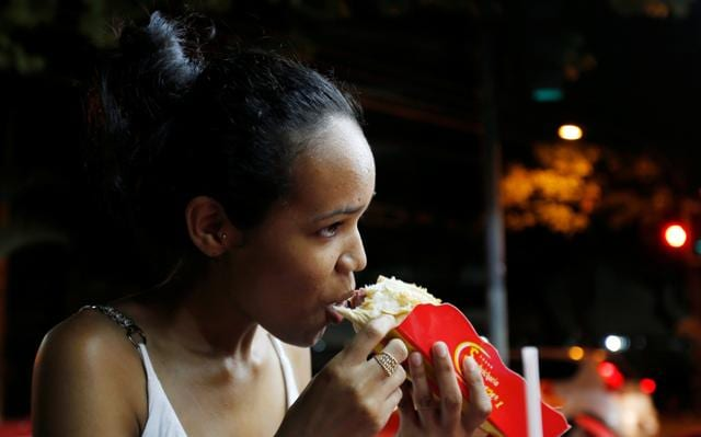 A woman eats a podrao, the Portuguese word for 'rotten' (a hotdog or burger-type sandwich assembled according to taste), in Rio de Janeiro, Brazil.
