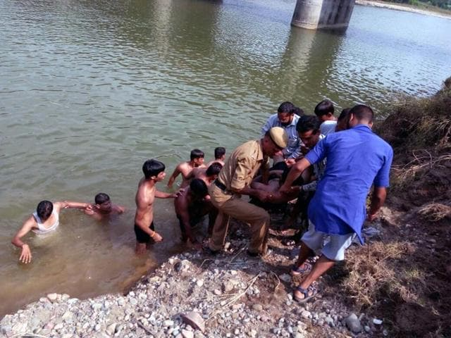 Police and local youth during a search and rescue operation in Dehra of Kangra district on Sunday afternoon