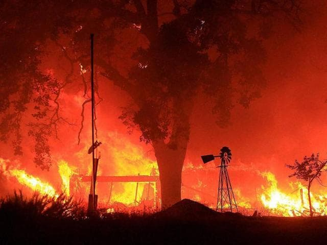 A two-story structure burns in a subdivision off Morgan Valley Road as a wildfire burns in Lower Lake, California.